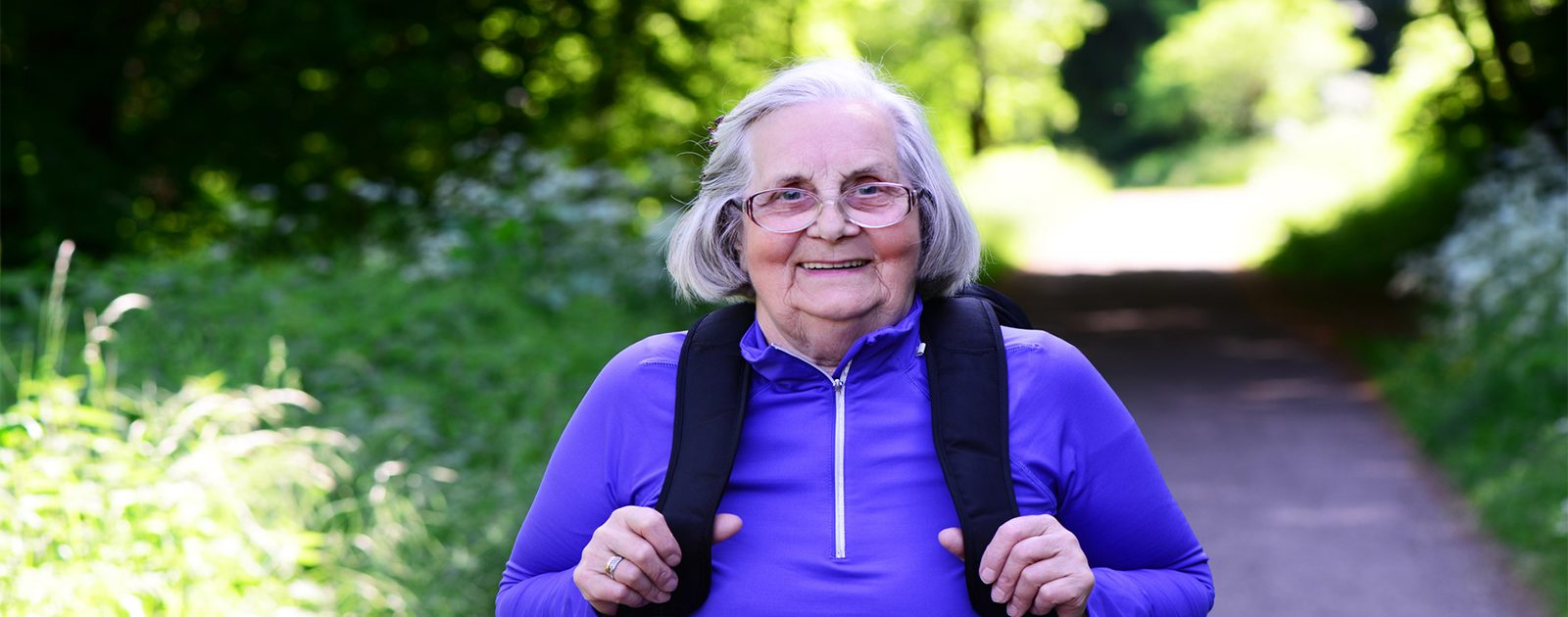Alltagstipps gegen Rückenschmerzen bei älteren Menschen: Frau bewegt sich an der Natur.