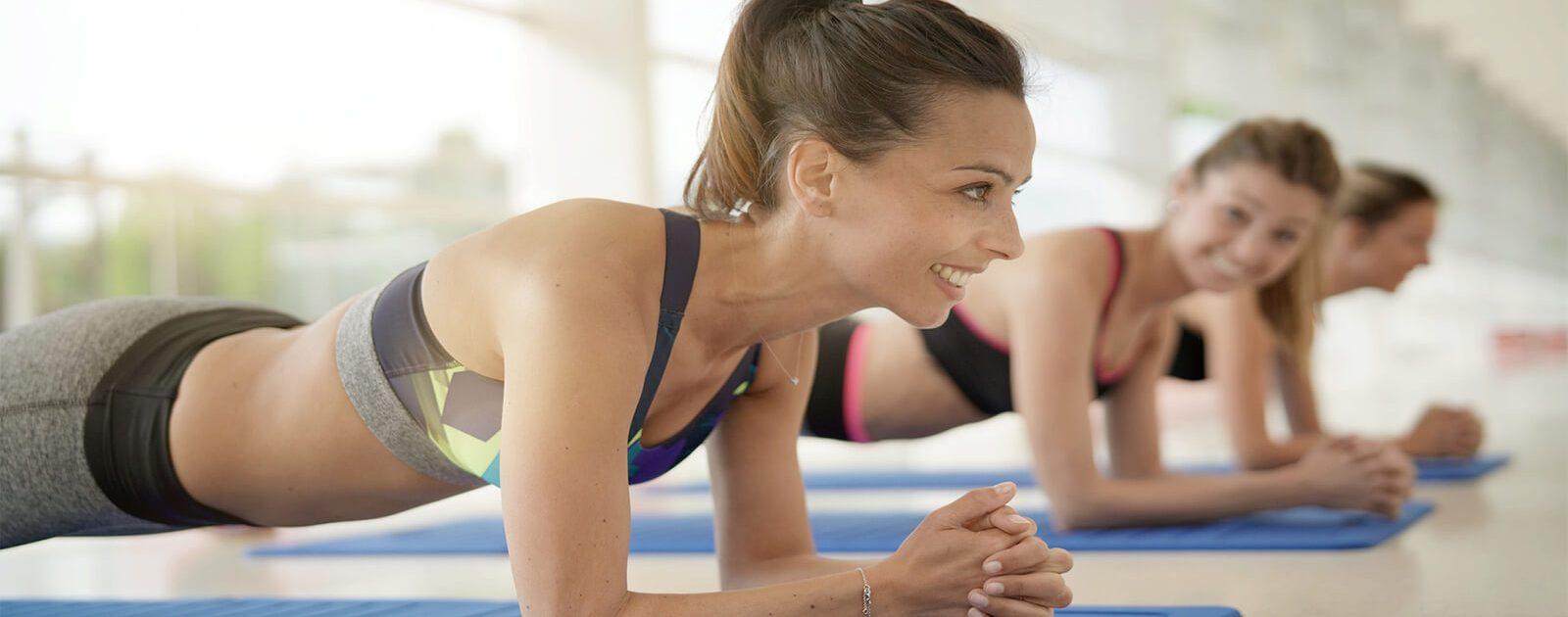 Frauen machen Sportübungen, um die Schmerzen ihres Hexenschusses zu lindern.