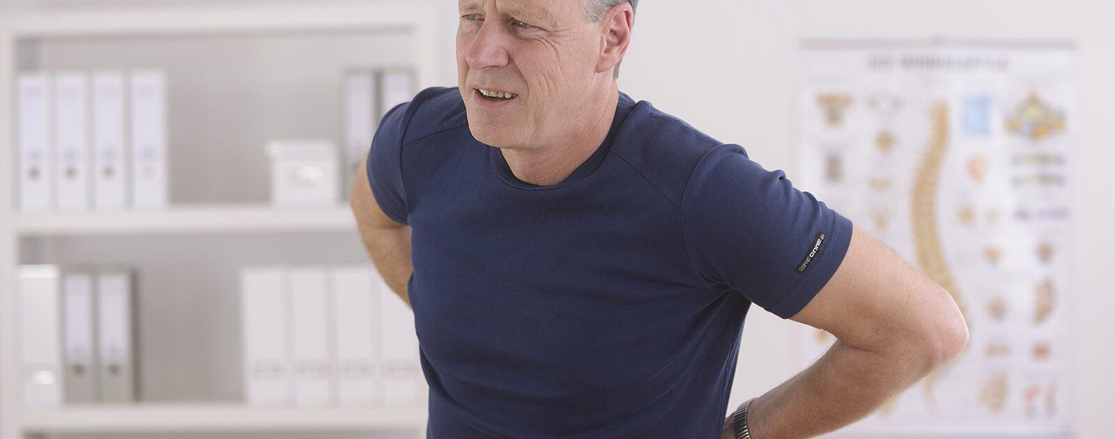Mann hält sich den schmerzenden Rücken und überlegt, ob er einen Test zum Thema Bandscheibenvorfall machen sollte.