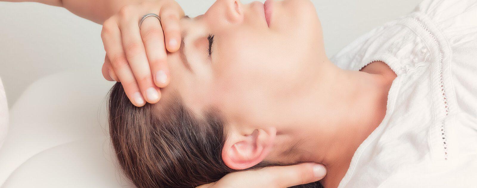 Frau lässt sich von einem Chiropraktiker am Nacken behandeln.