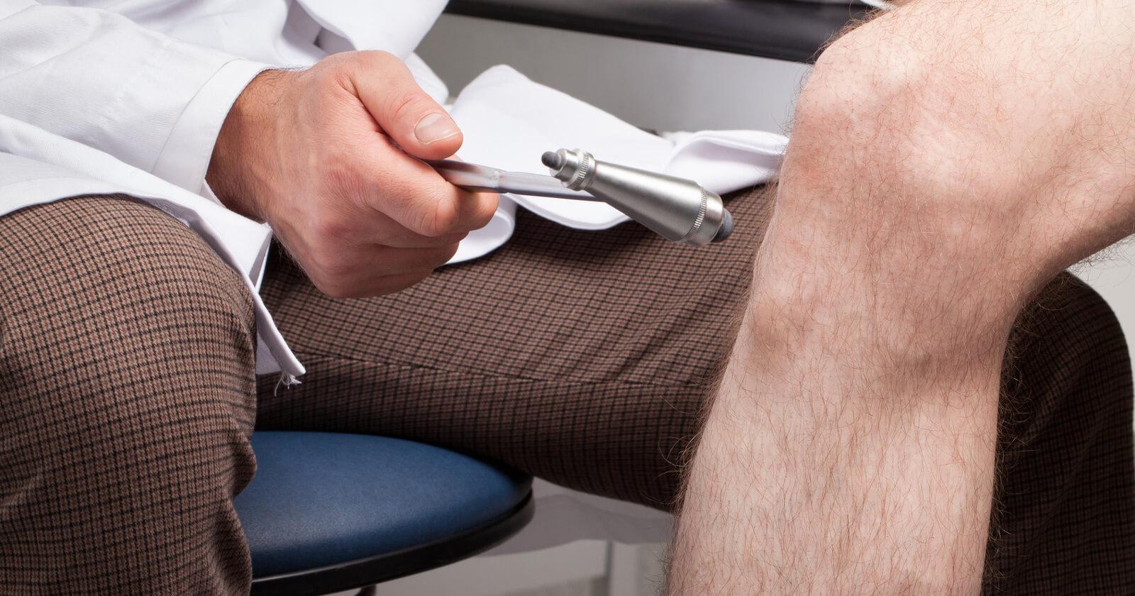 Arzt testet Reflexe am Knie zur Diagnose einer diabetischen Neuropathie.