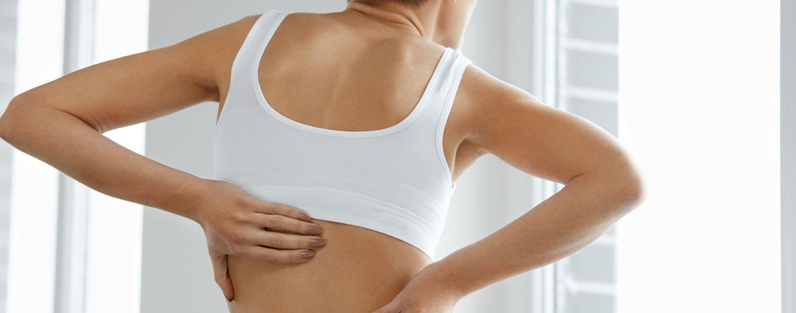 Eine Frau fasst sich an den Rücken aufgrund eines eingeklemmten Nervs.