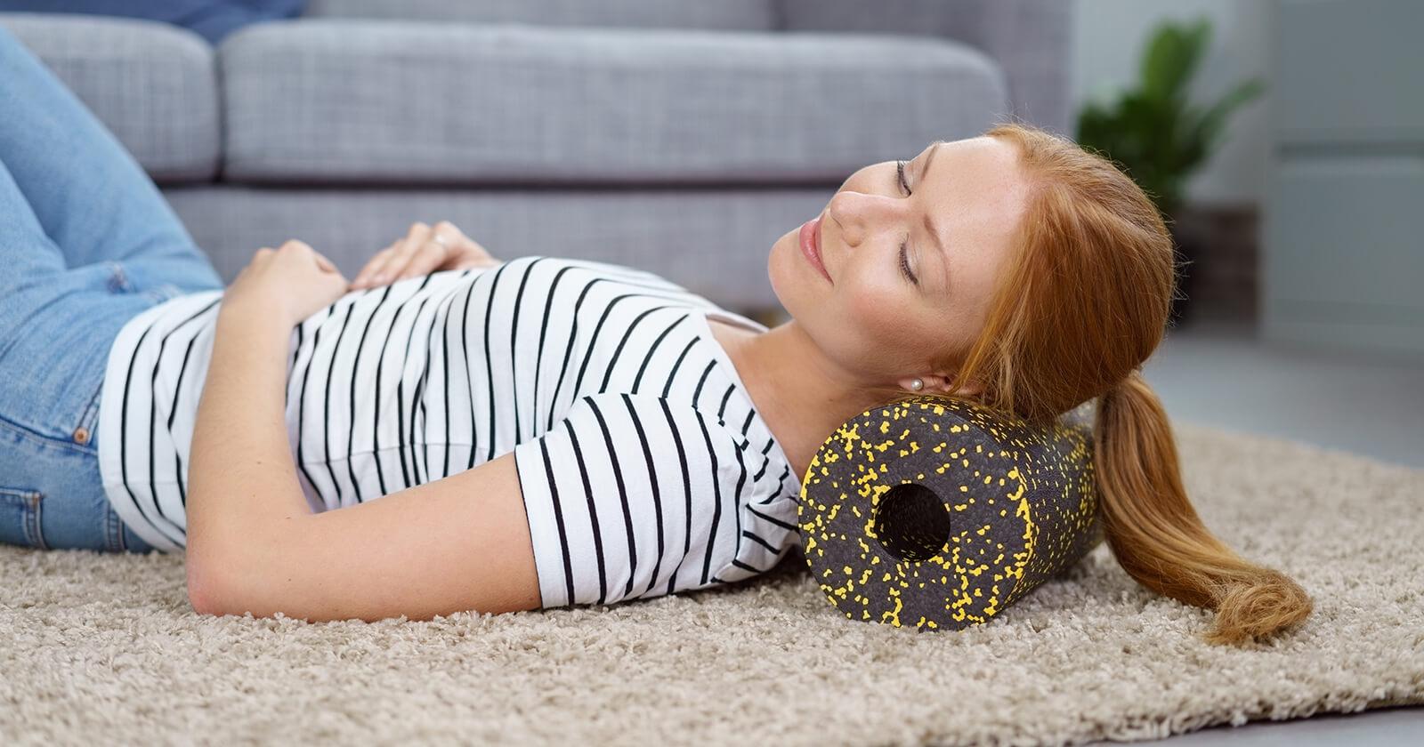 Frau entspannt ihren Nacken mit einer Faszienrolle.