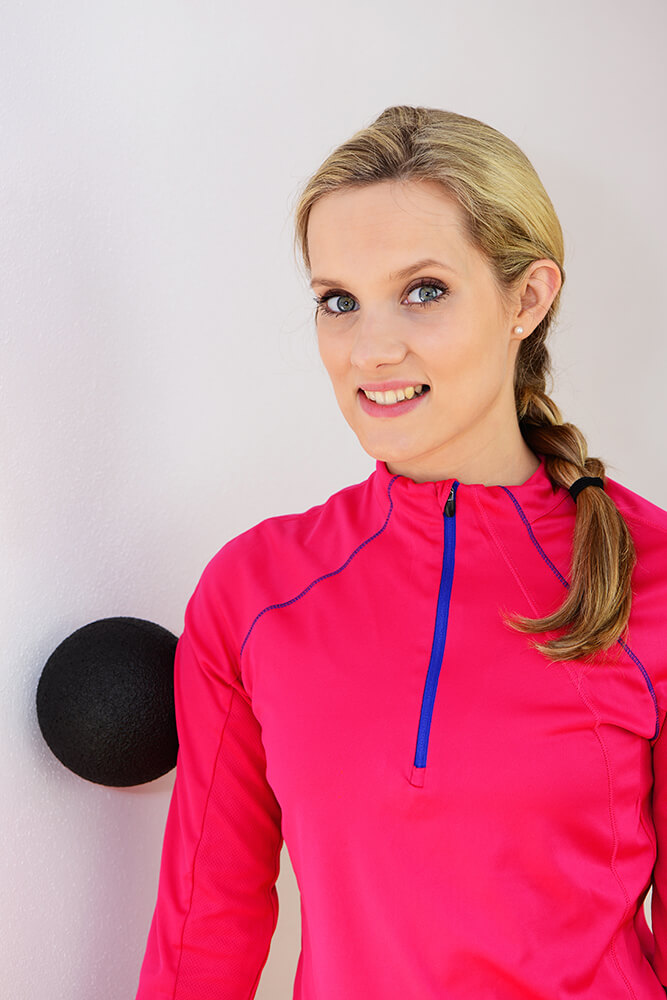 Frau mach Übung mit einer Faszienrolle für den Schulterbereich.