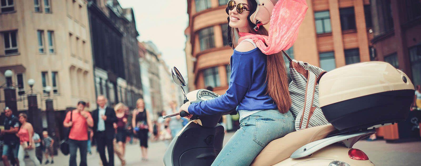 Junge Frau auf einem Roller ist bei der Fahrt Zugluft ausgesetzt und schützt ihren Hals mit einem Schal.