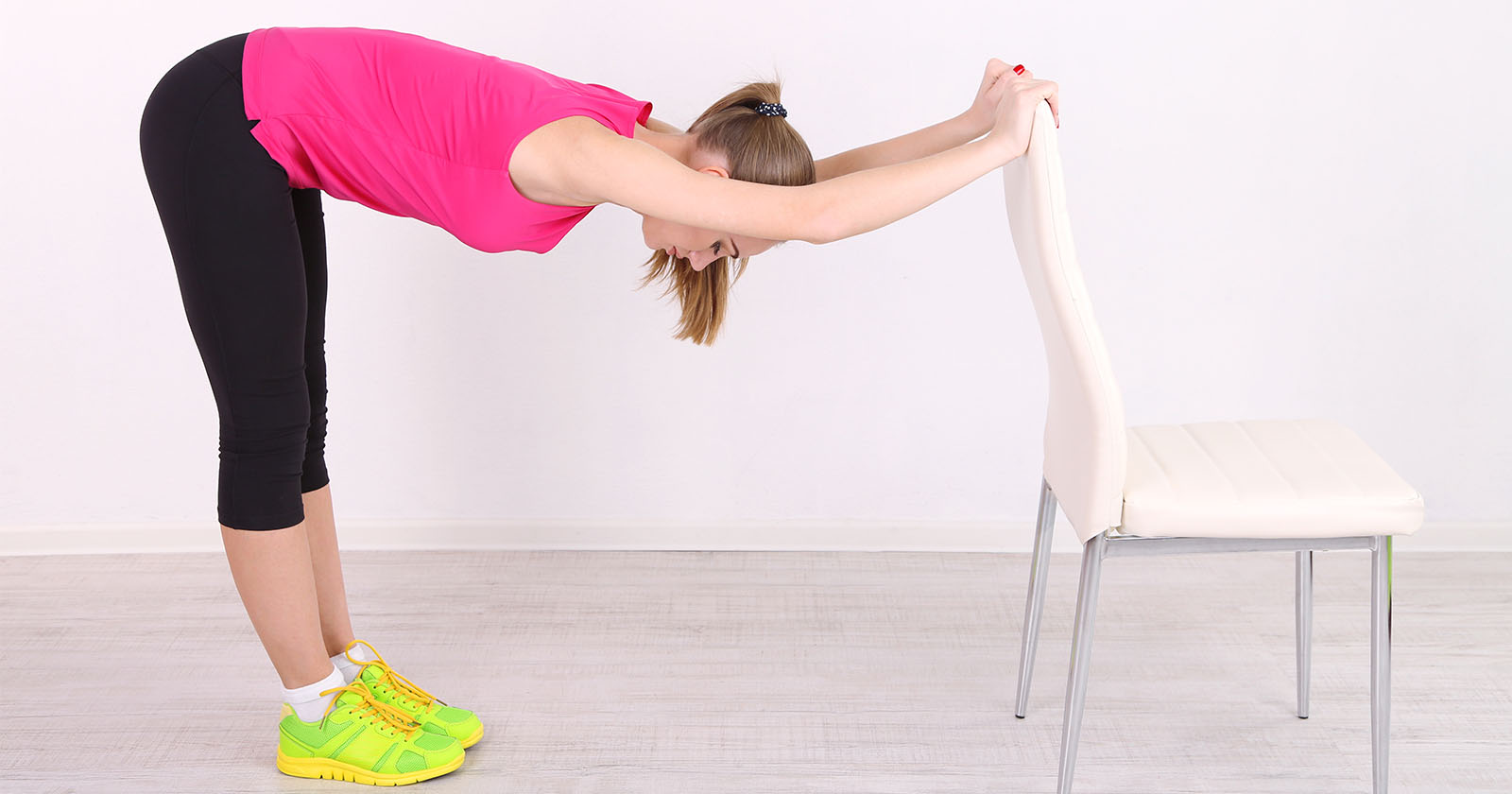 Junge Frau entspannt ihre Rückenmuskeln mit einer Dehnübung.