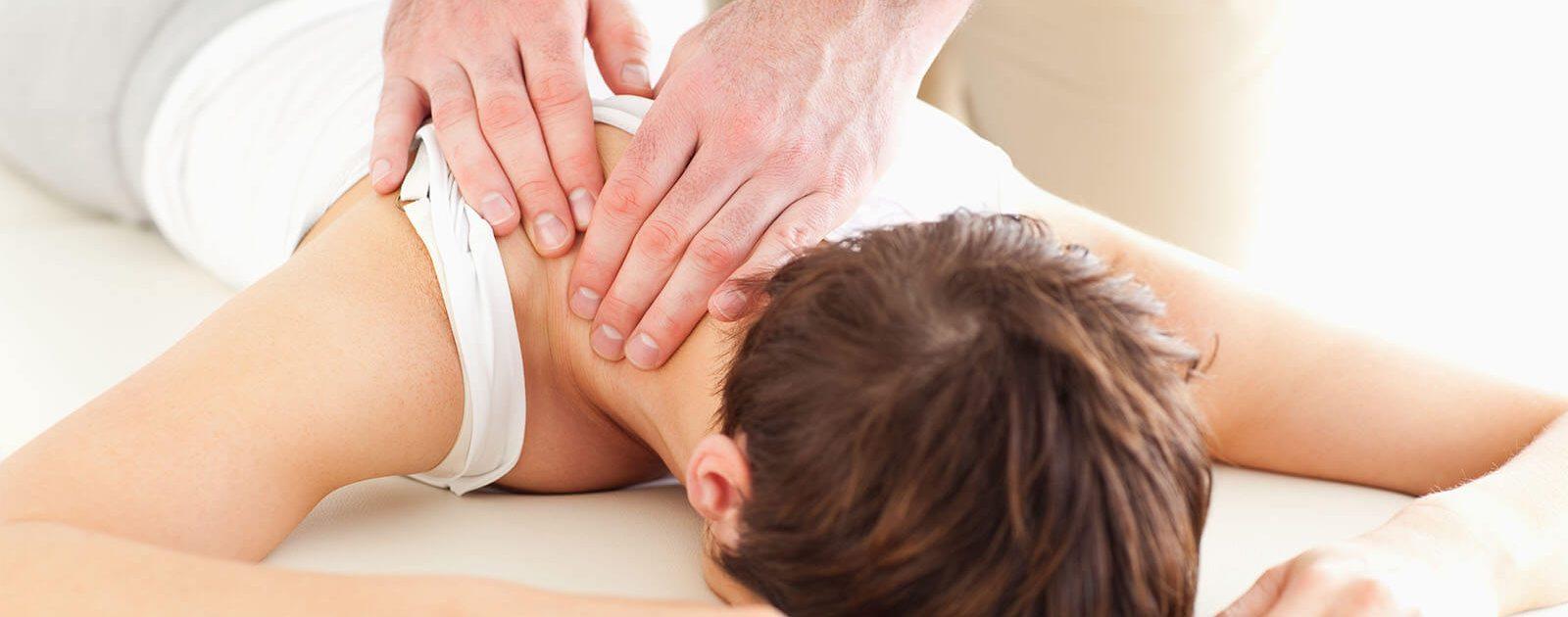 Frau mit Rückenschmerzen lässt sich mit Akupressur behandeln.