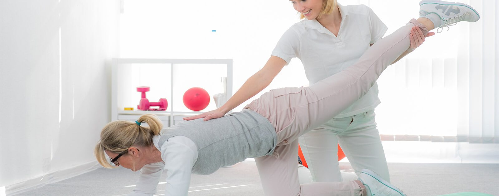 Frau leistet Patientin Hilfe bei Rückenschmerzen