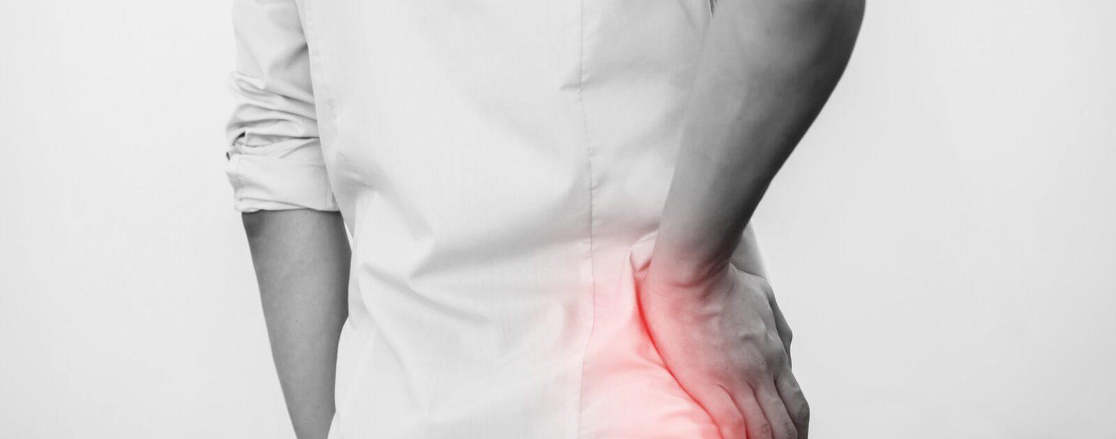Einem jungen Mann machen Hüftgelenkschmerzen zu schaffen, er hält sich die schmerzende Seite.
