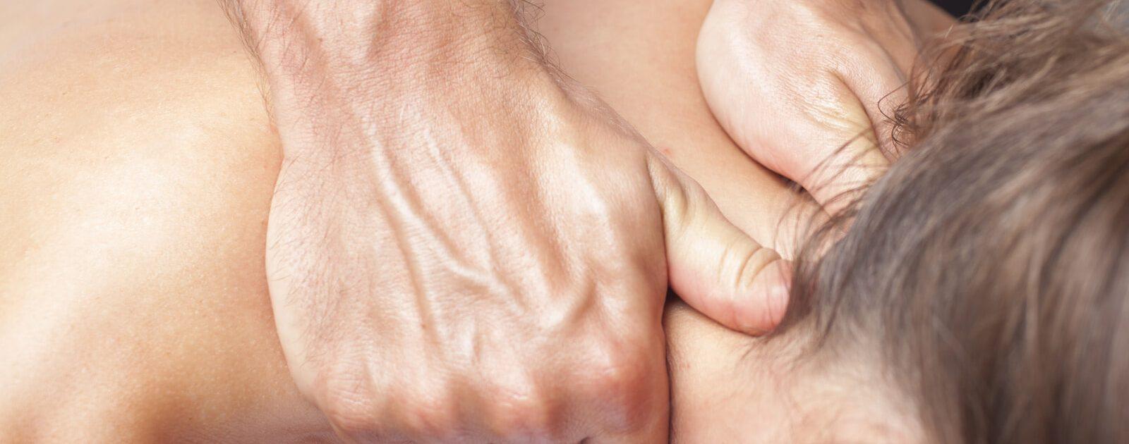 Frau lässt sich am Nacken gegen die Symptome eines HWS Syndroms behandeln