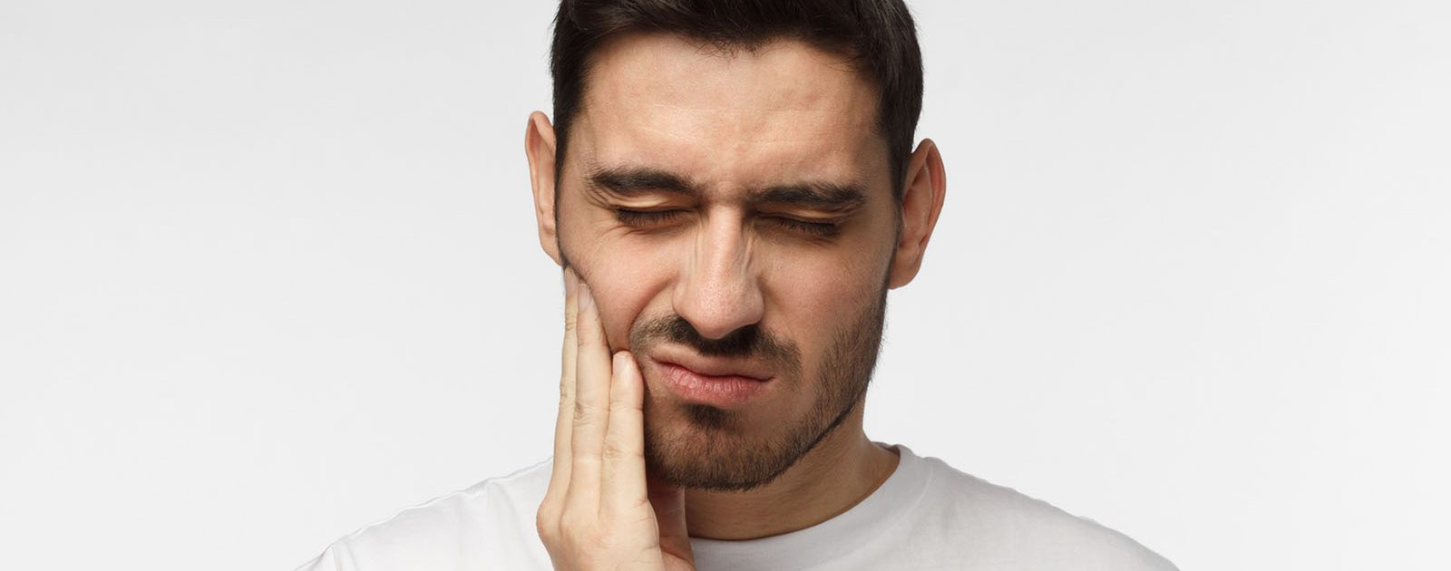Ein hat Kiefergelenkschmerzen und fasst sich an die Wange