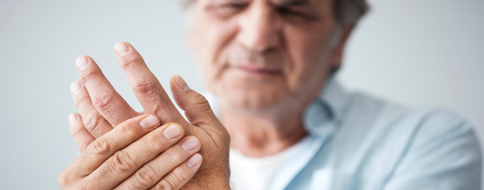 Mann hält sich den kribbelnden Arm aufgrund einer Nervenschädigung.