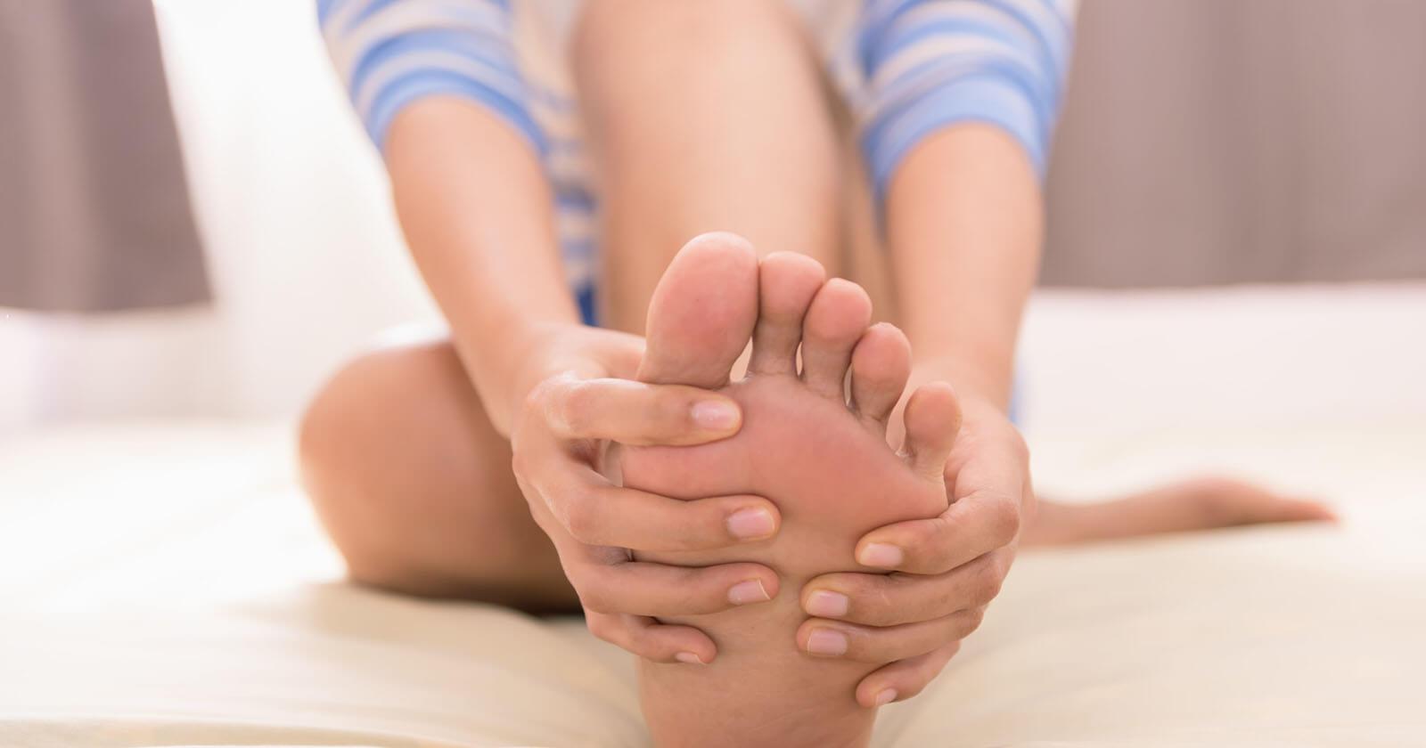 Frau fasst sich an schmerzenden Fuß wegen diabetischer Neuropathie.