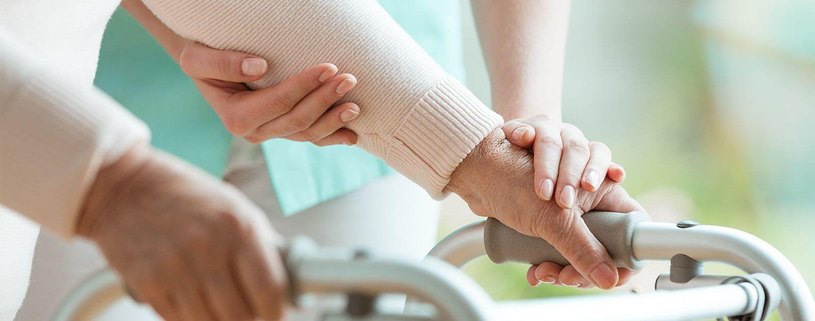 Ältere Frau muss sich aufgrund ihrer ausgeprägten Parkinson-Symptome auf eine Gehhilfe stützen.
