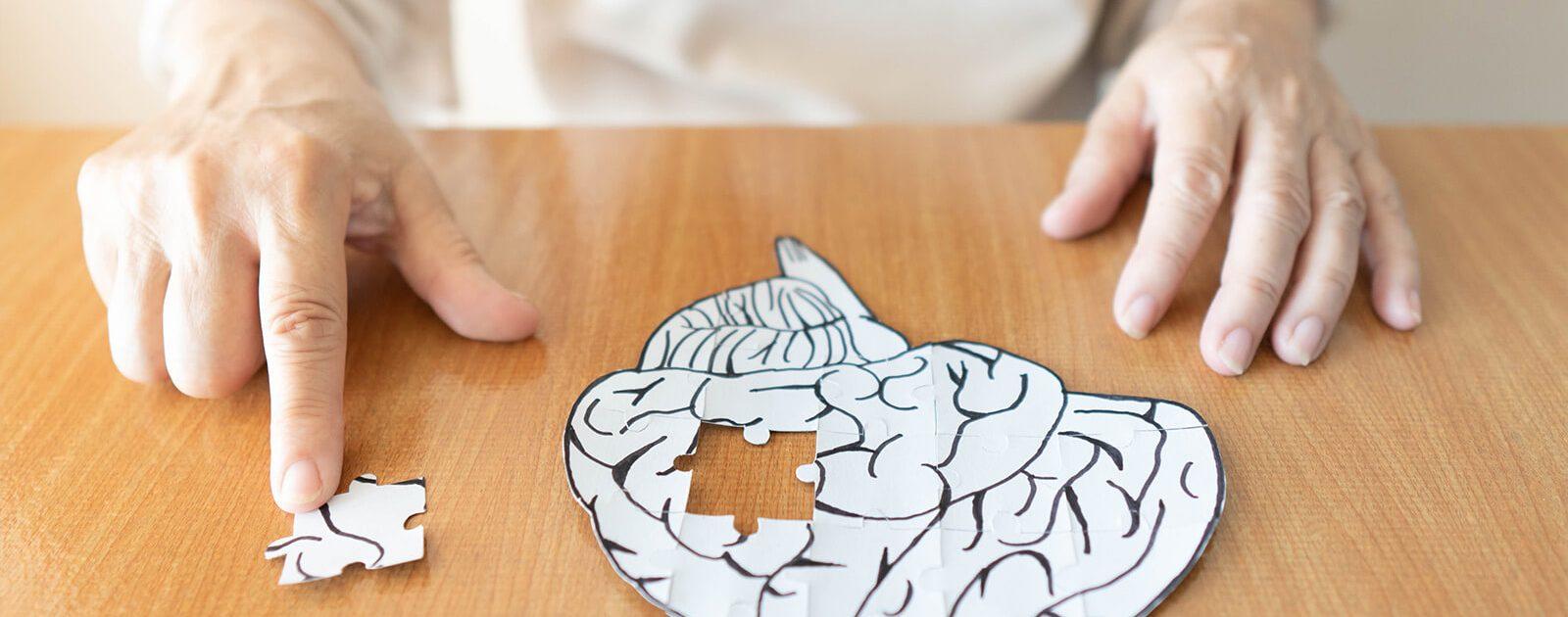 Ältere Frau entfernt symbolisch für Alzheimer ein Puzzleteil aus einem als Gehirn geformten Puzzle.