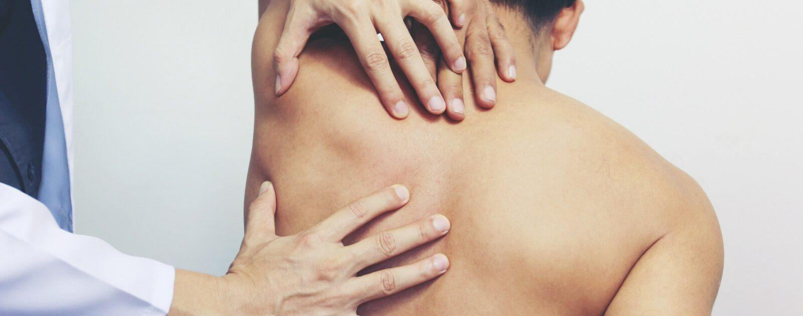 Mann lässt seine Rückenschmerzen im Oberkörper von einem Arzt untersuchen.