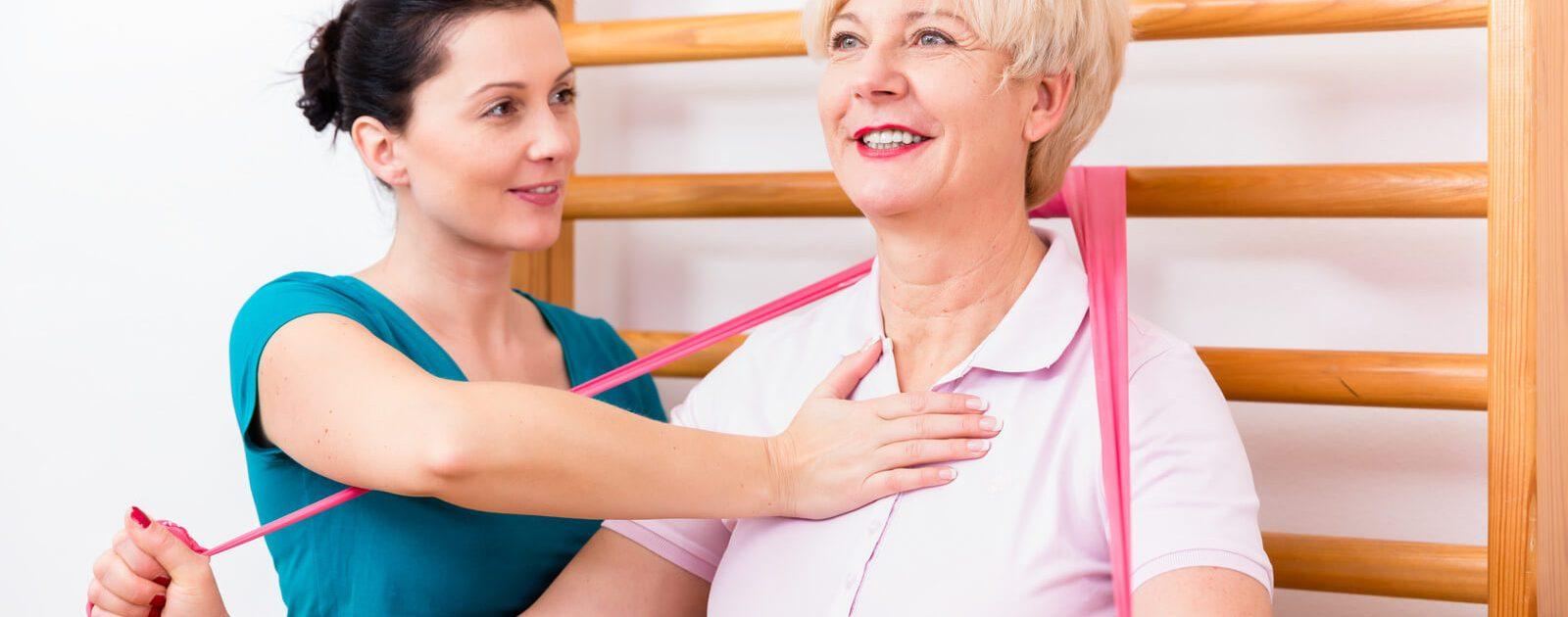In der Physiotherapie zeigt die Therapeutin einer älteren Frau mit Rückenschmerzen, wie sie die Übung korrekt ausführt.