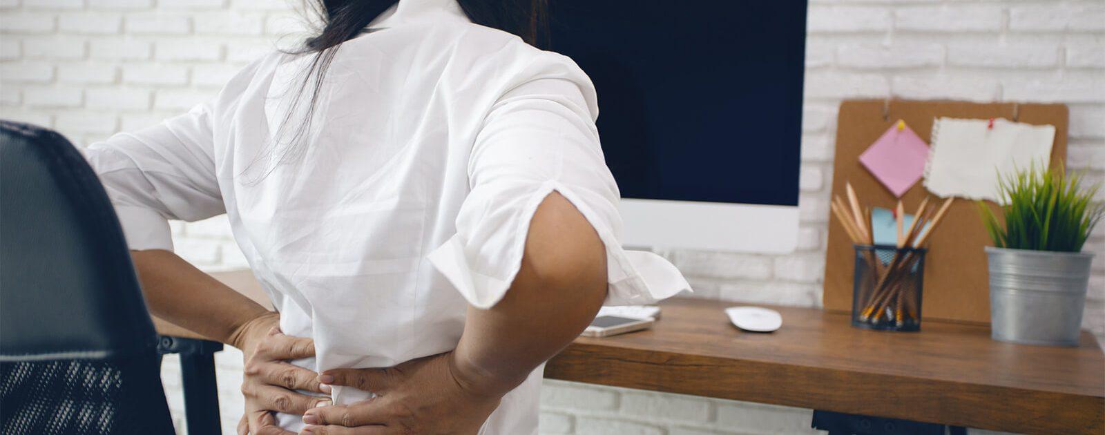 Rückenschmerzen bei Frauen: Frau sitzt mit Rückenschmerzen am Schreibtisch