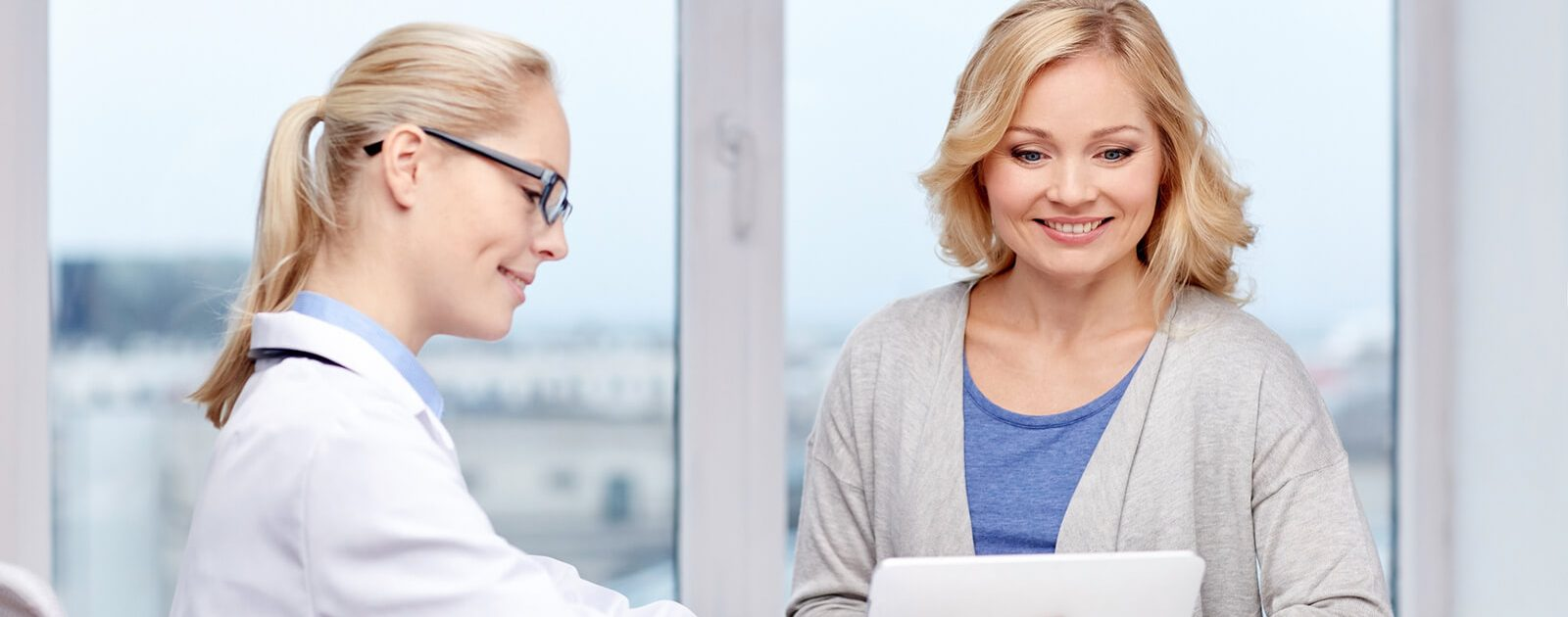 Ärztin klärt Frau mit Rückenschmerzen über alternative Heilverfahren auf
