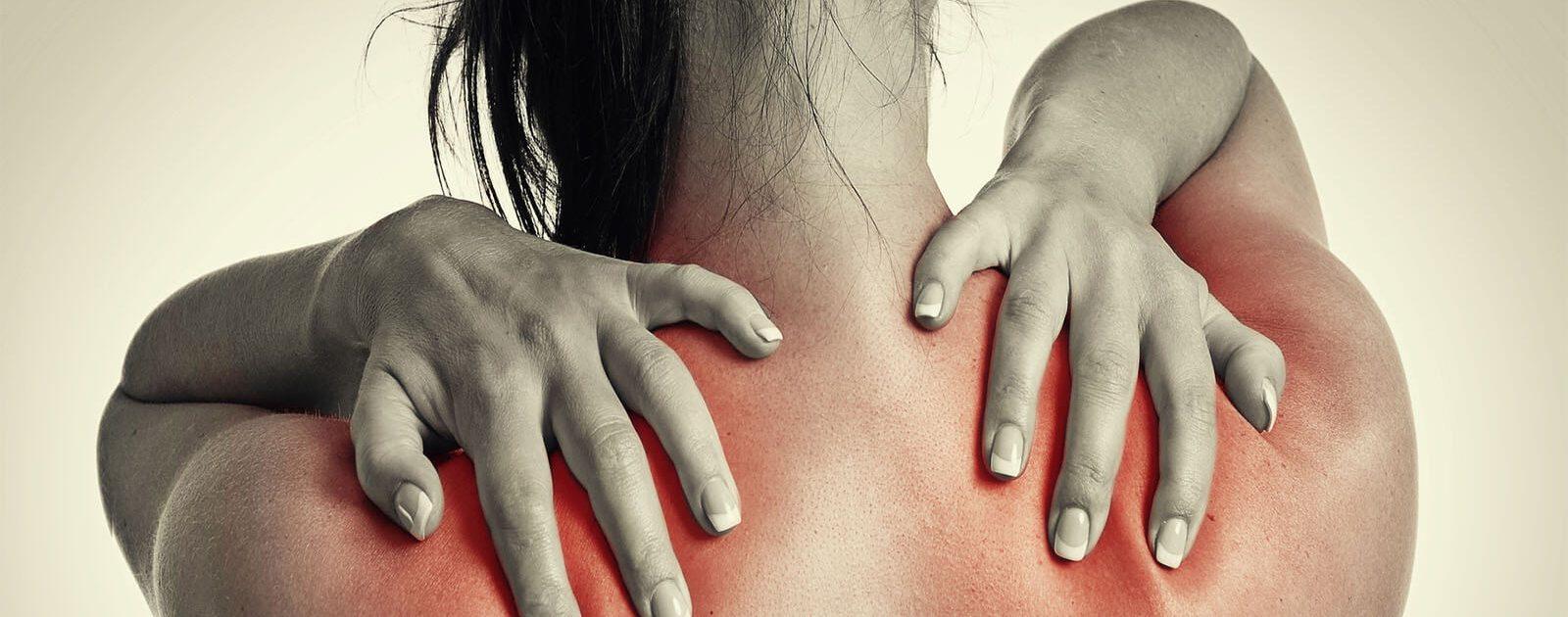 Frau fasst sich an die verspannte Schultermuskulatur. Bei diesen Rückenschmerzen kann Magnesium helfen!