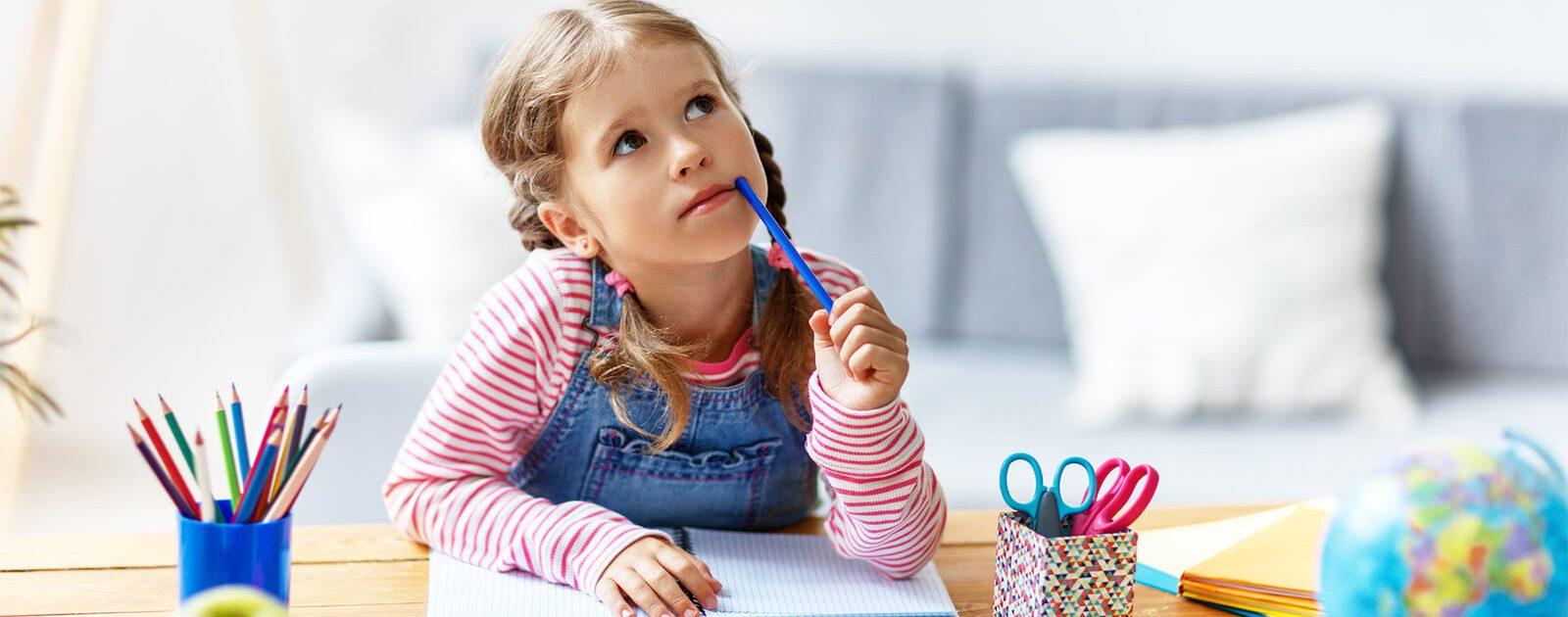 Kind mit Rueckenschmerzen am Schreibtisch