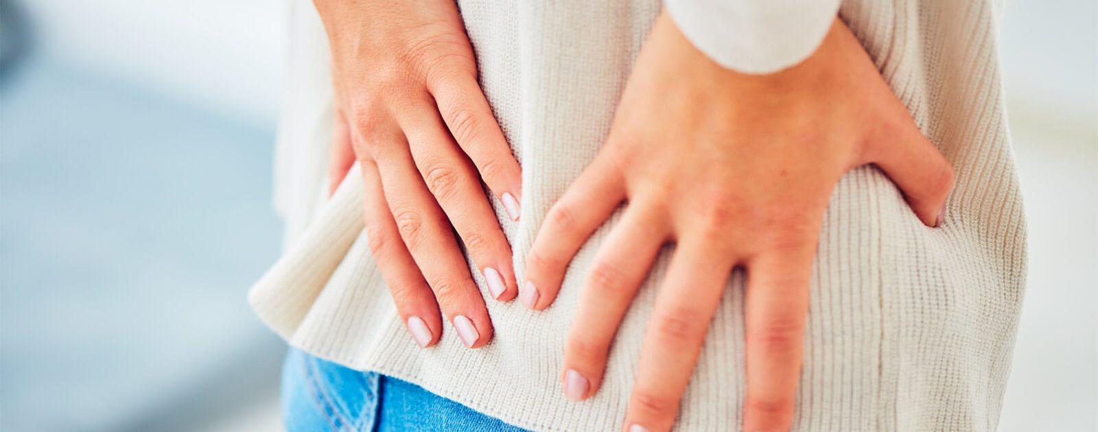 Frau mit Rückenschmerzen während der Menstruation