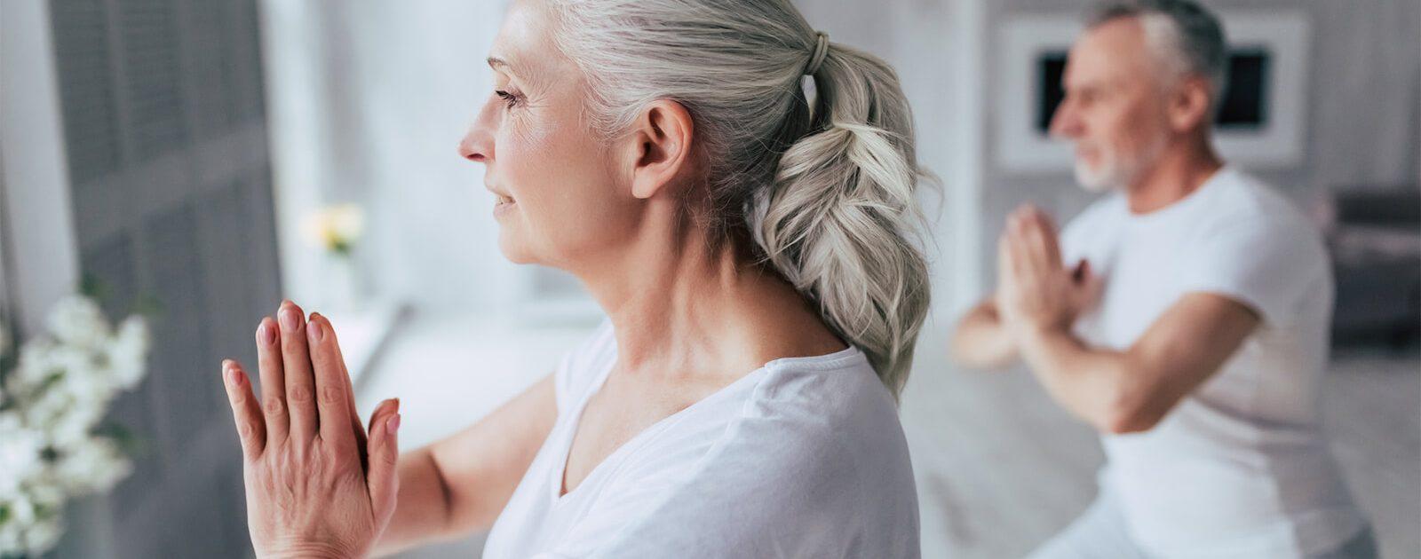 Eine Frau und ein Mann im Alter machen Übungen, um Rückenschmerzen vorzubeugen.