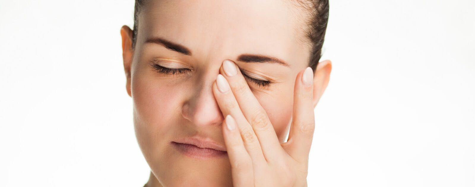 Eine Frau mit einer Trigeminusneuralgie hält sich das schmerzende Gesicht