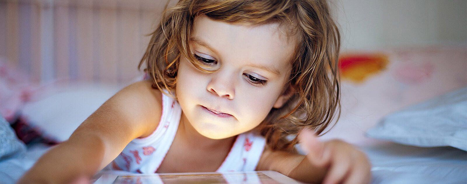 Kind mit Tablet leidet wegen Bewenungsmangel unter Rückenschmerzen