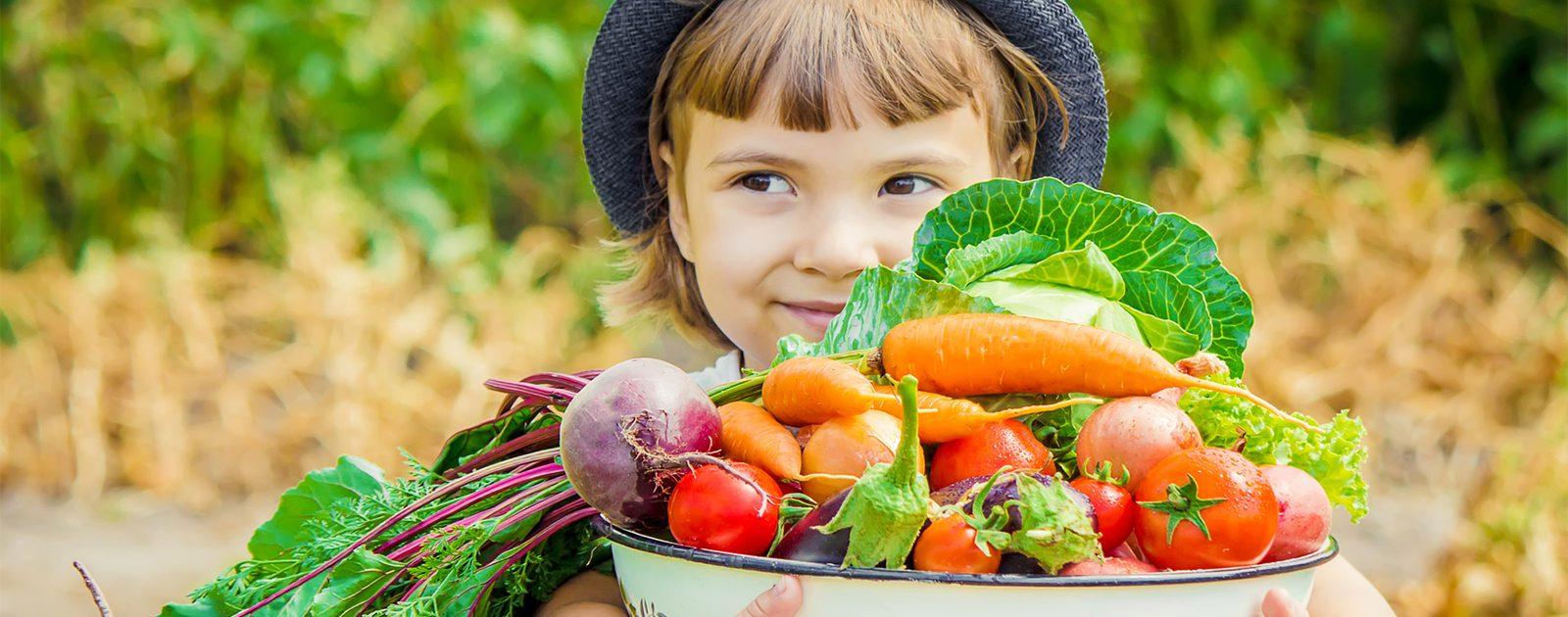 Mädchen hält Schale mit viel Obst, um Vitaminmangel vorzubeugen