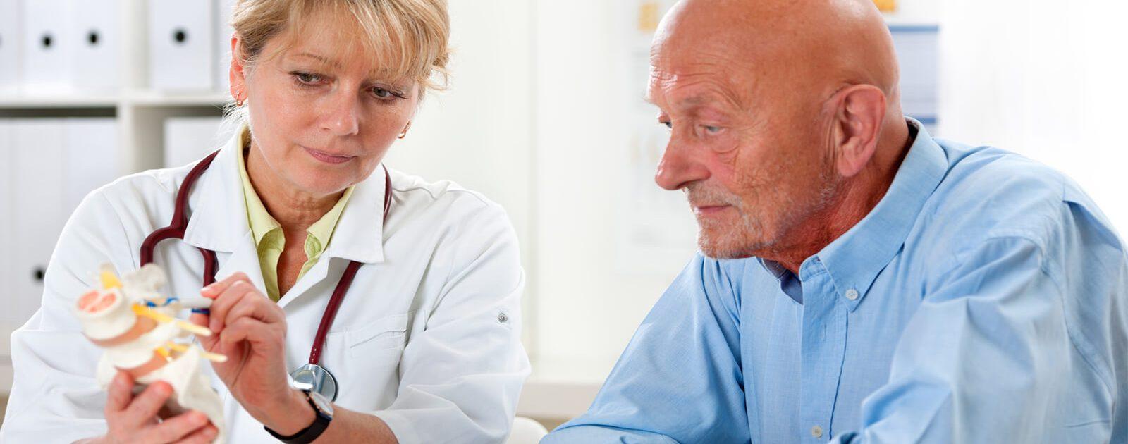 Eine Ärztin berät den Patienten wegen seinen Rückenschmerzen