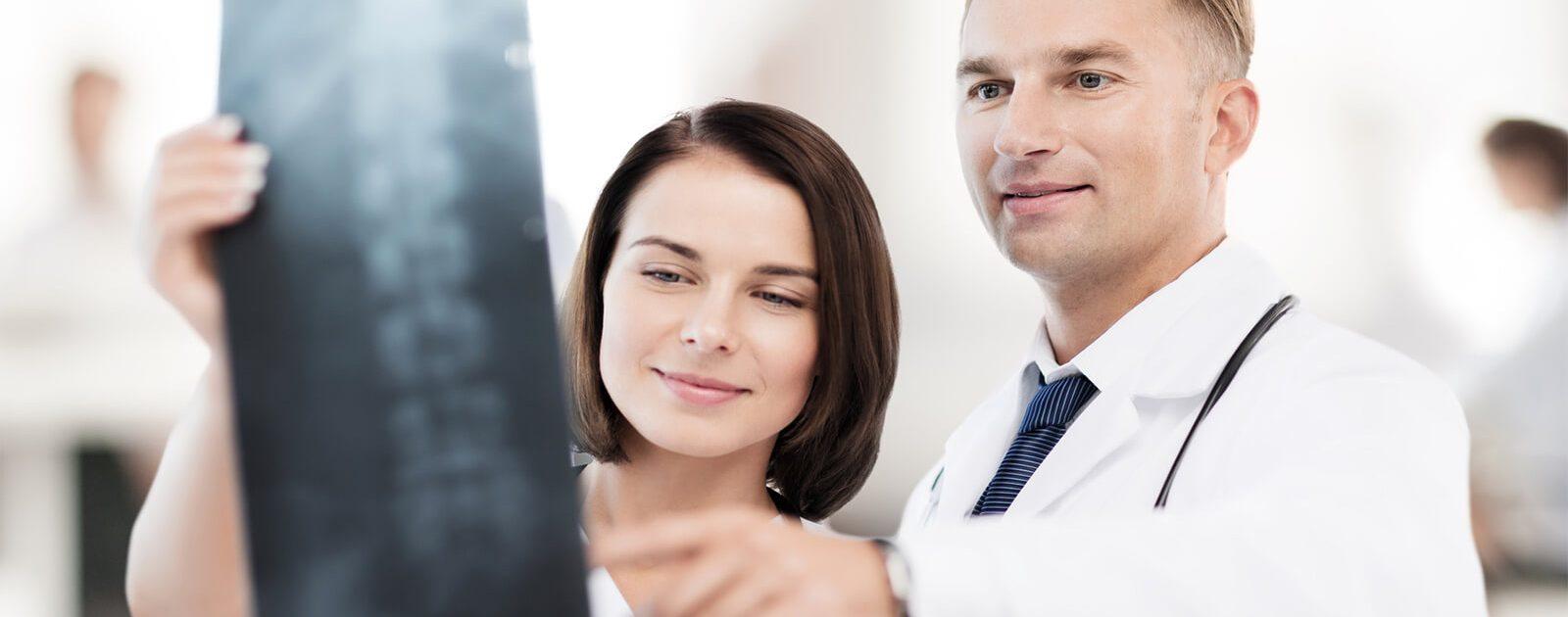 Ärzte mit einem Röntgenbild der Wirbelsäule