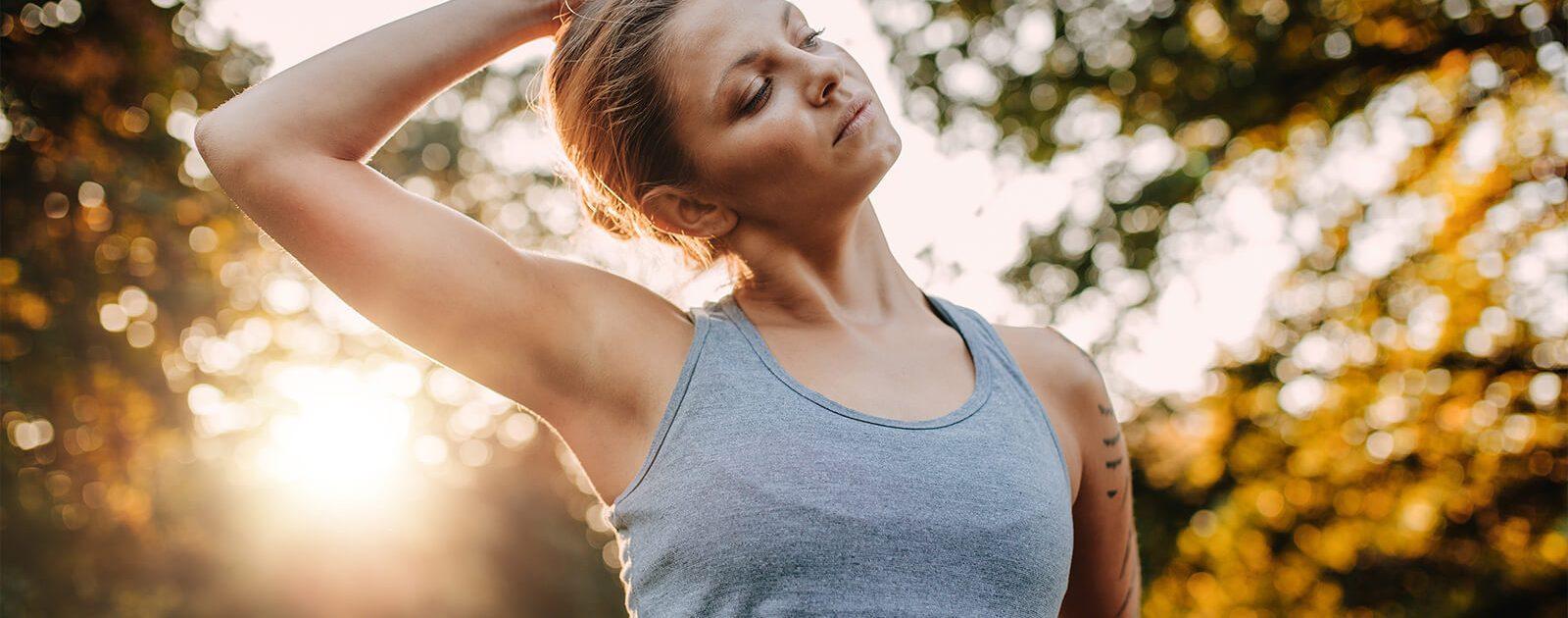 Frau macht Schulterübung gegen Ihre Schmerzen.