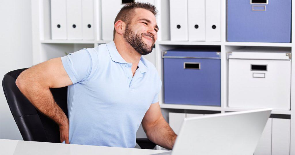 Mann, der sich aufgrund einer Ischialgie an den Rücken fasst.