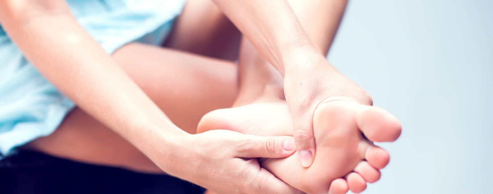 Am Tarsaltunnelsyndrom leidende Frau hält sich die schmerzende Fußsohle.