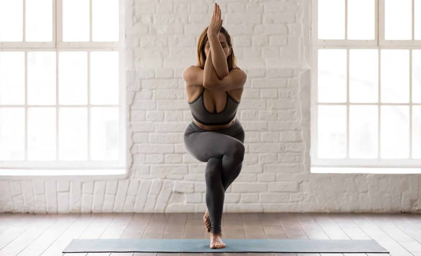 """Frau öffnet mit der Yoga-Übung """"Adler-Arme"""" ihren Schulterbereich."""