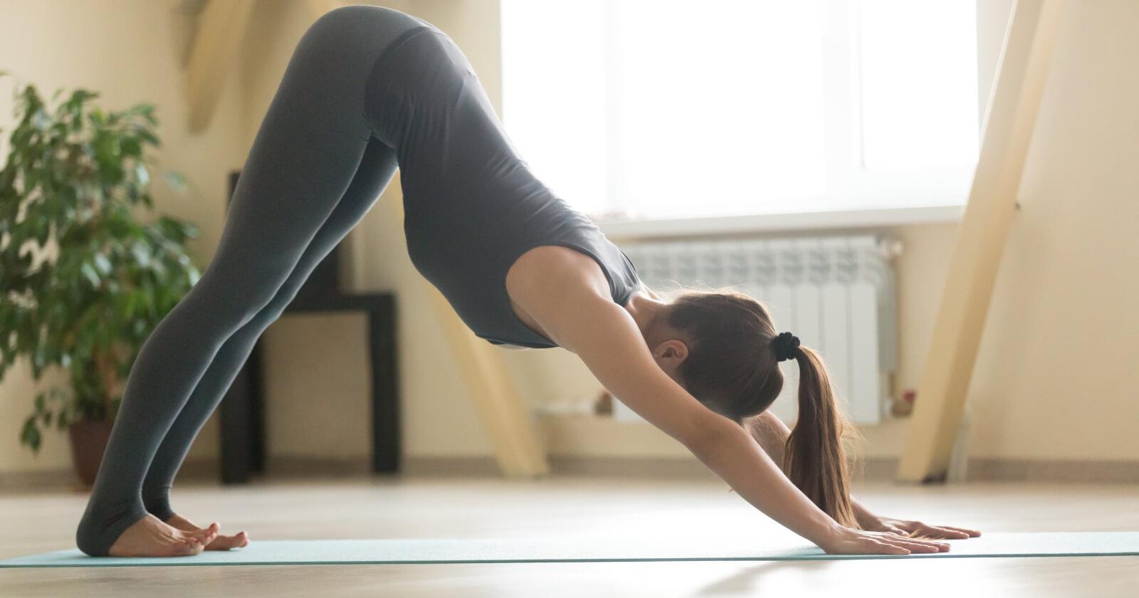 """Frau macht die Übung """"herabschauender Hund"""" ¬ eine Grundposition im Yoga."""