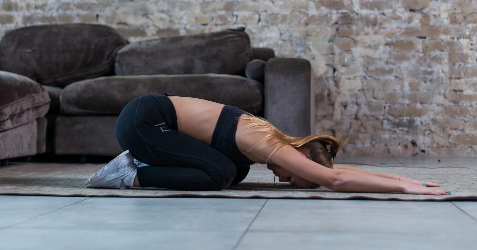 """Frau in der Yoga-Grundhaltung """"Stellung des Kindes""""."""