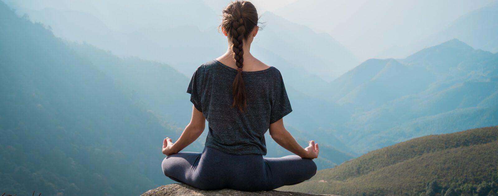 Frau macht in der Natur Yoga gegen Rückenschmerzen.