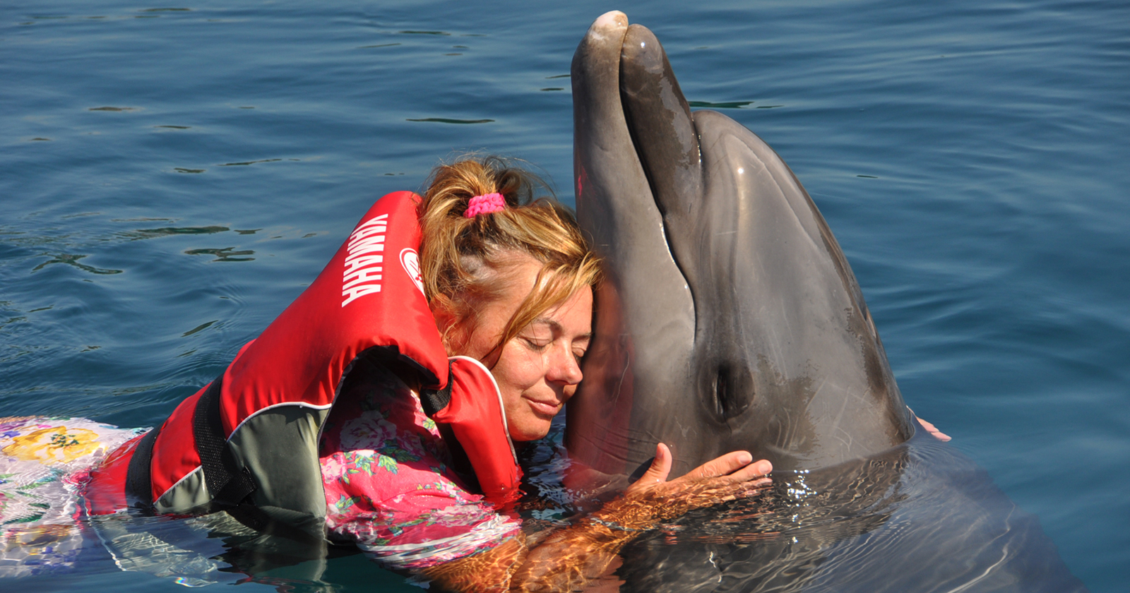 Zuzana Babicek beim Schwimmen mit einem Delphin.