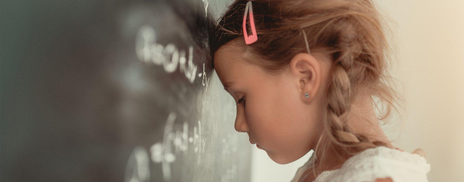Mädchen hat aufgrund ihres ADHS Probleme, sich in der Schule zu konzentrieren und lehnt sich mit dem Kopf gegen die Tafel.