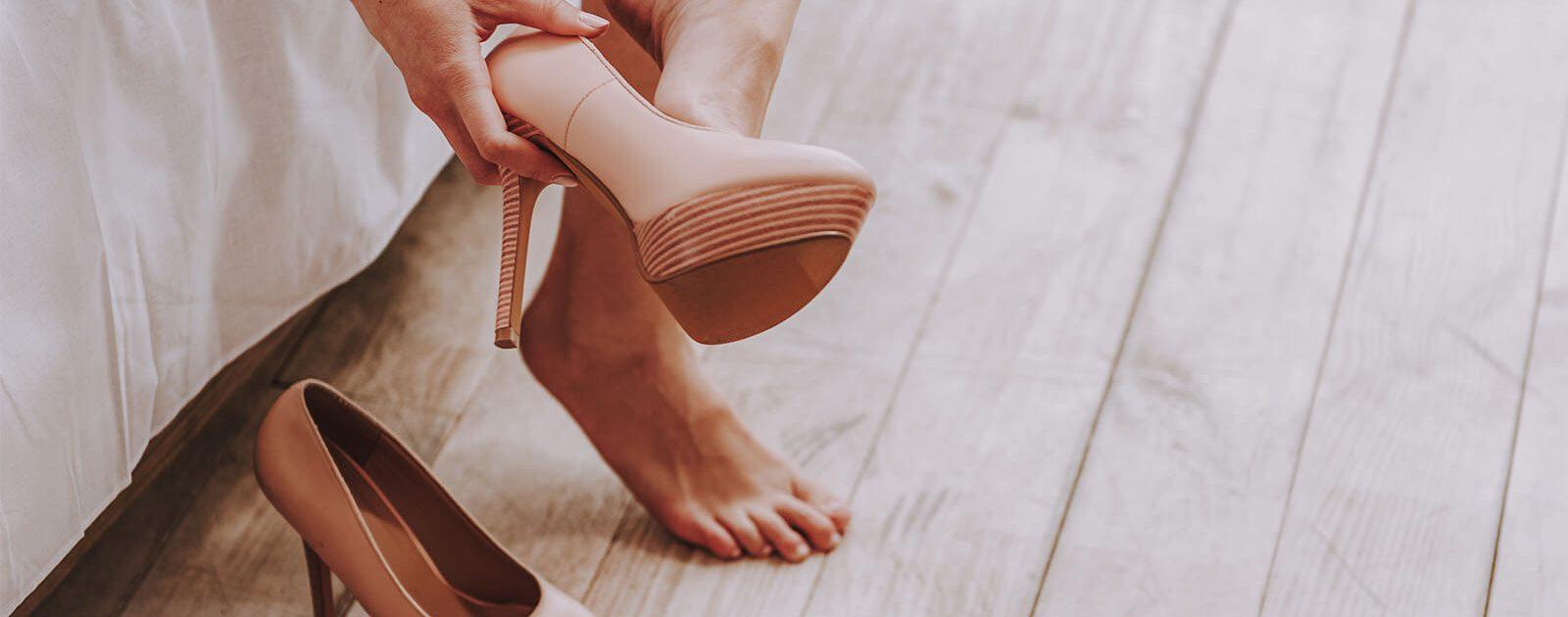 Frau mit schmerzenden Füßen zieht zu enge, hohe Schuhe aus, die das Risiko für das Kamerad-Schnürschuh-Syndrom erhöhen.