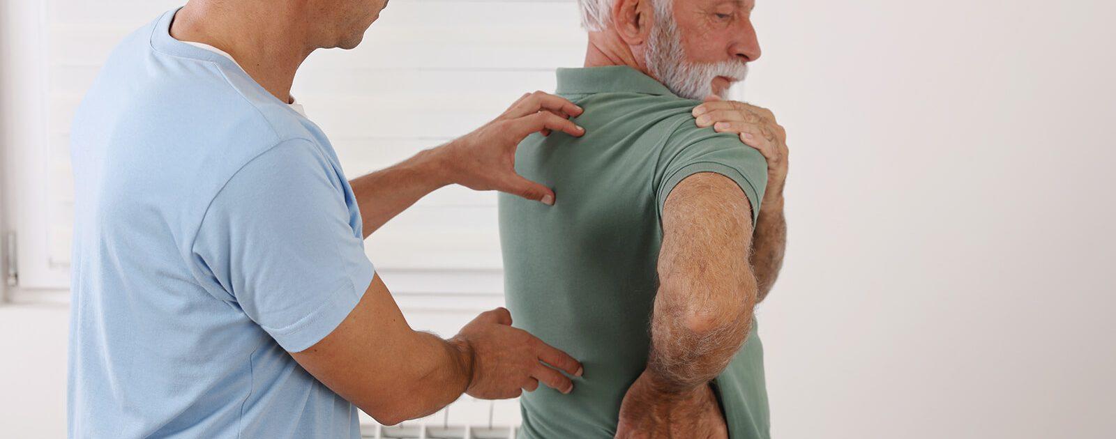 Ein Orthopäde untersucht den Rücken seines Patienten, er vermutet eine Osteochondrose als Ursache der Beschwerden.